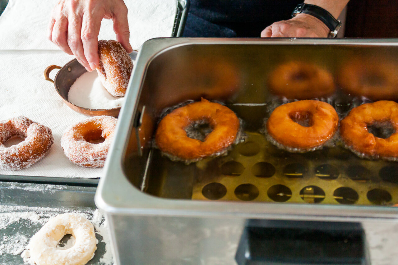 Deep frying homemade donuts in a big deep frying appliance then dipping the fried donuts in sugar to coat them before serving