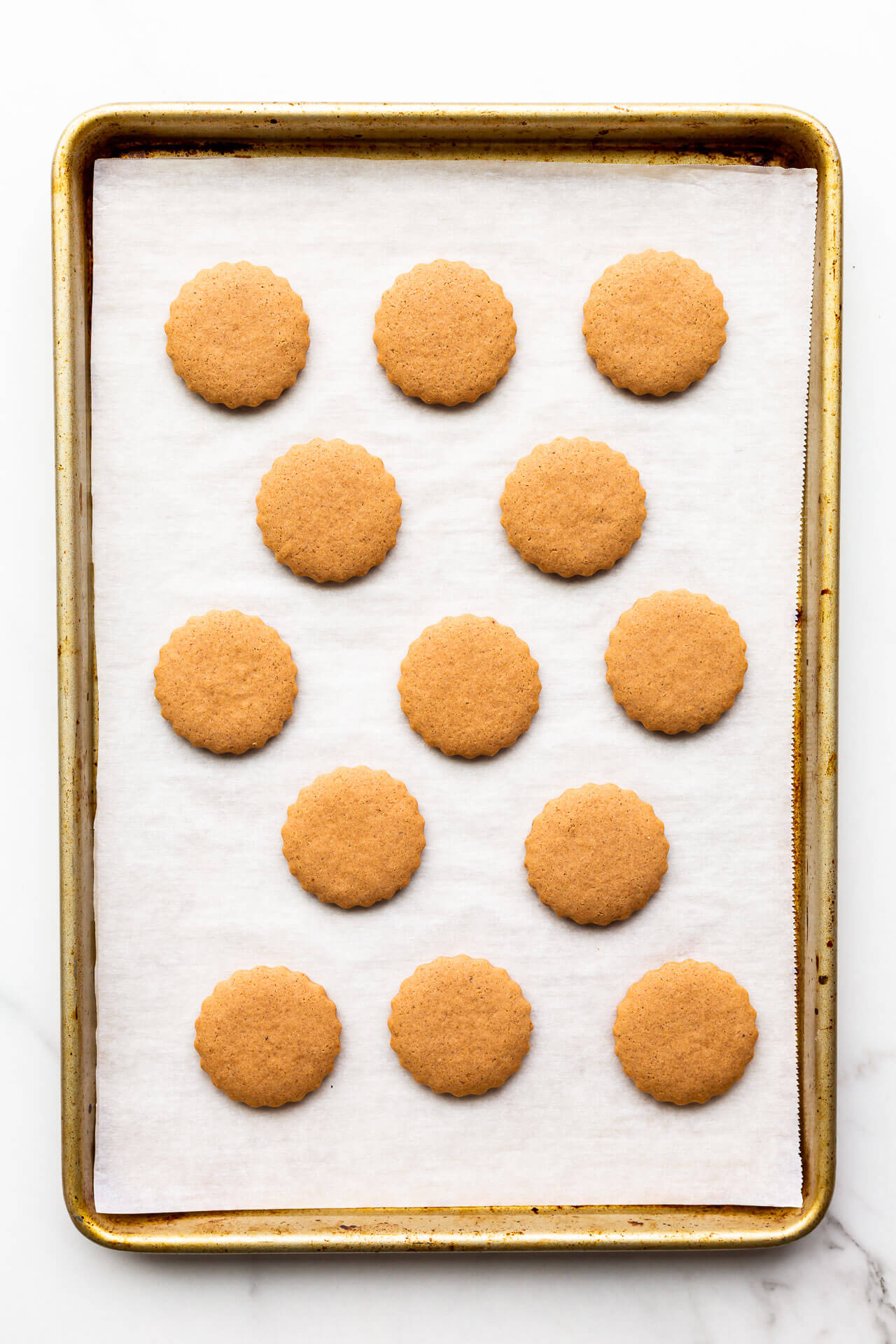 Freshly baked German gingerbread cookies on a parchment lined sheet pan.
