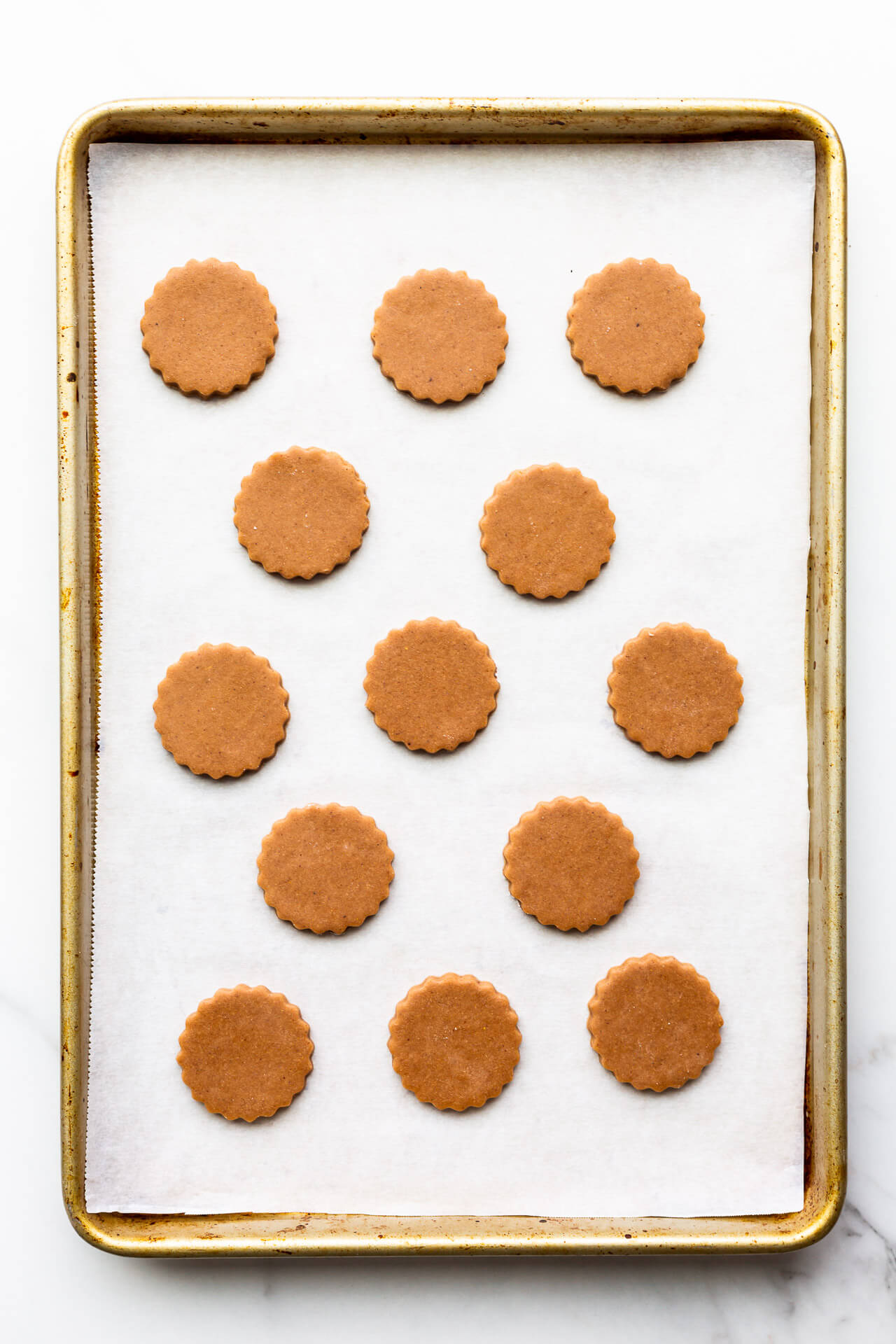 German gingerbread cookie cutouts on a parchment-lined sheet pan ready for the oven.