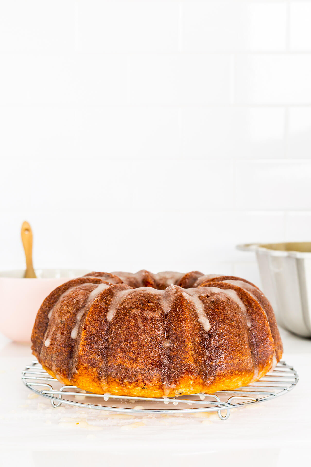 Glazing a bundt cake, set on a wire rack, painting on a sugar glaze using a pastry brush/