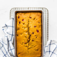 Pumpkin cranberry bread in a 9x5 loaf pan set on a cooling rack with a blue and white kitchen towel
