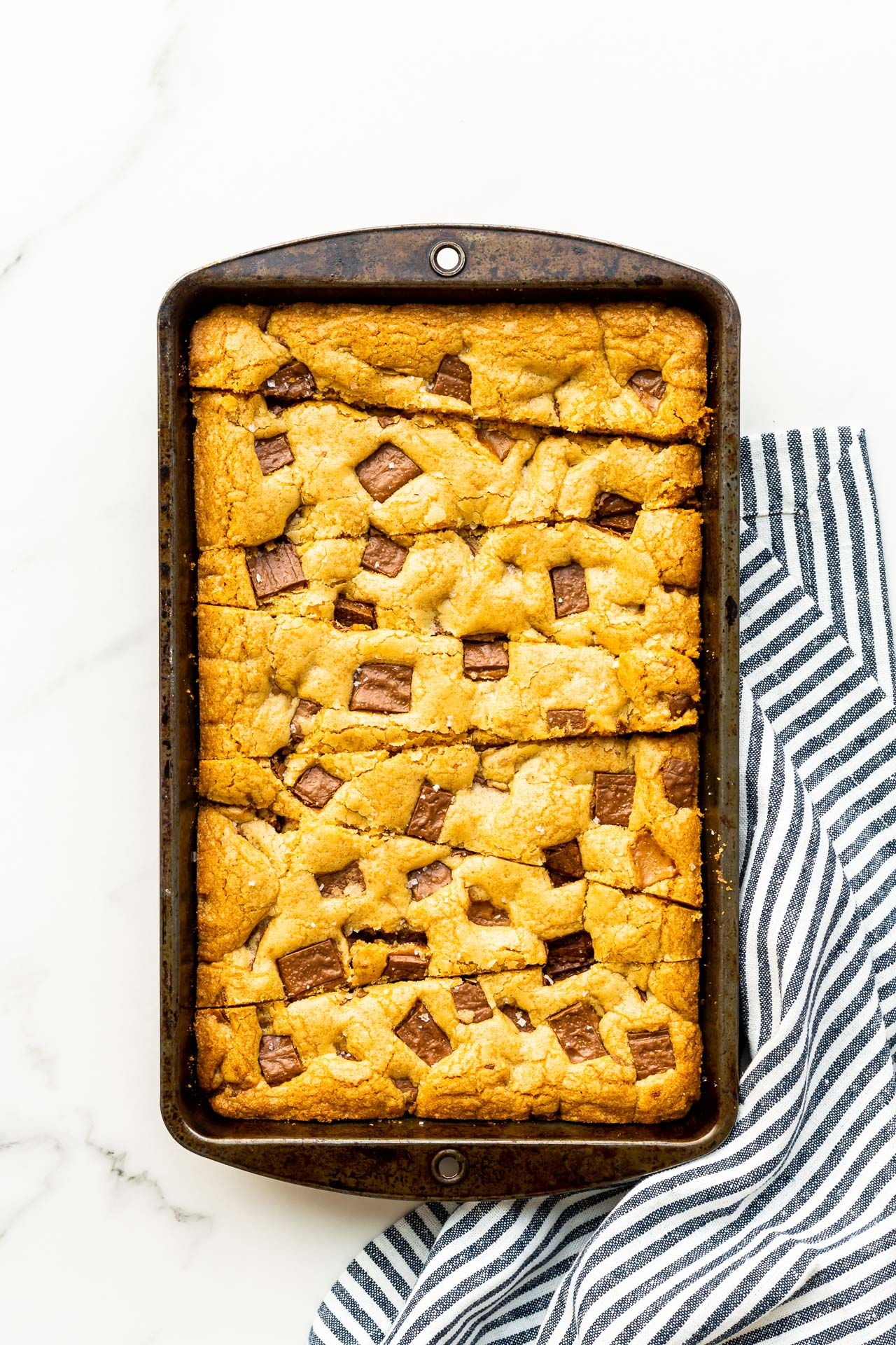 Skor blondie bars baked in a rectangular pan and cut into triangular strips