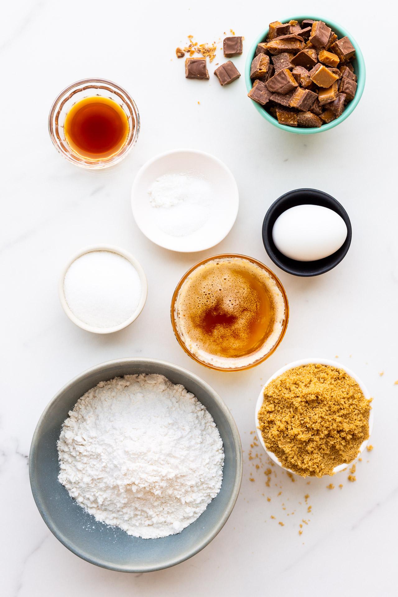Ingredients measured out to make Skor cookie bars, with browned butter, dark brown sugar, vanilla, an egg, leaveners, salt, flour, and lots of chopped Skor bars