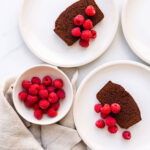 Slices of chocolate pound cake served on cream coloured plates with a bowl of fresh raspberries