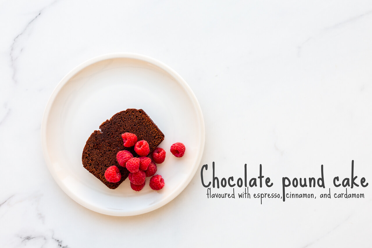 A slice of chocolate pound cake served on an off-white plate with fresh raspberries