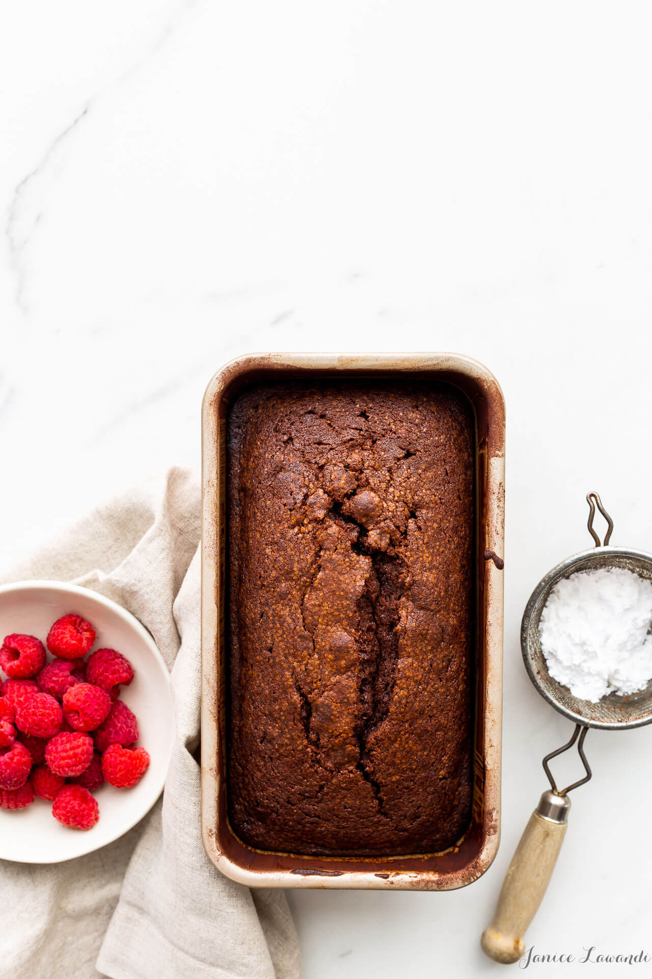 Chocolate pound cake baked in a loaf cake pan, dusted with powdered sugar using a mini strainer and served with a bowl of fresh raspberries