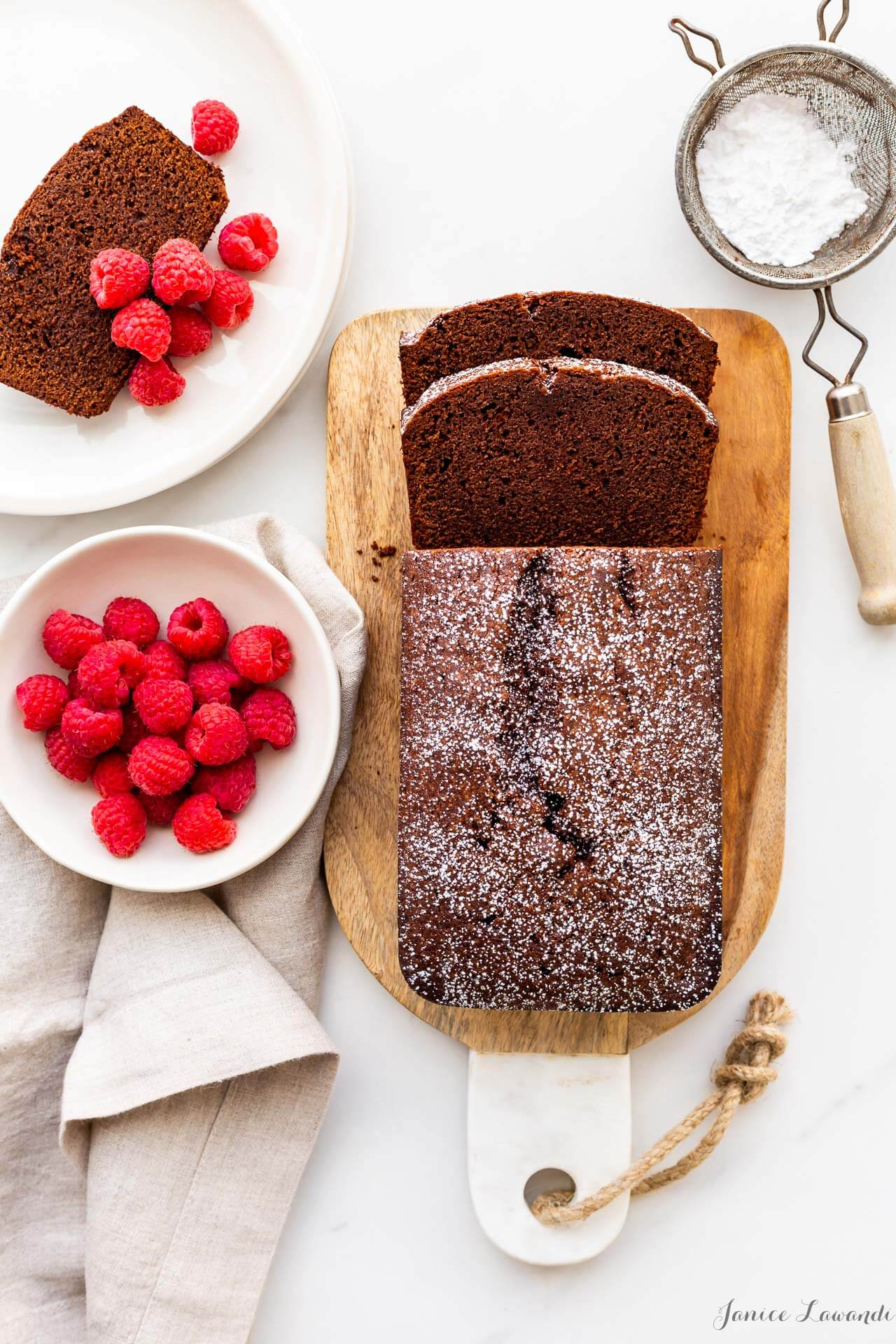 Slices of chocolate pound cake loaf cake flavoured with cinnamon and espresso, served on a cutting boards, slices topped with fresh raspberries