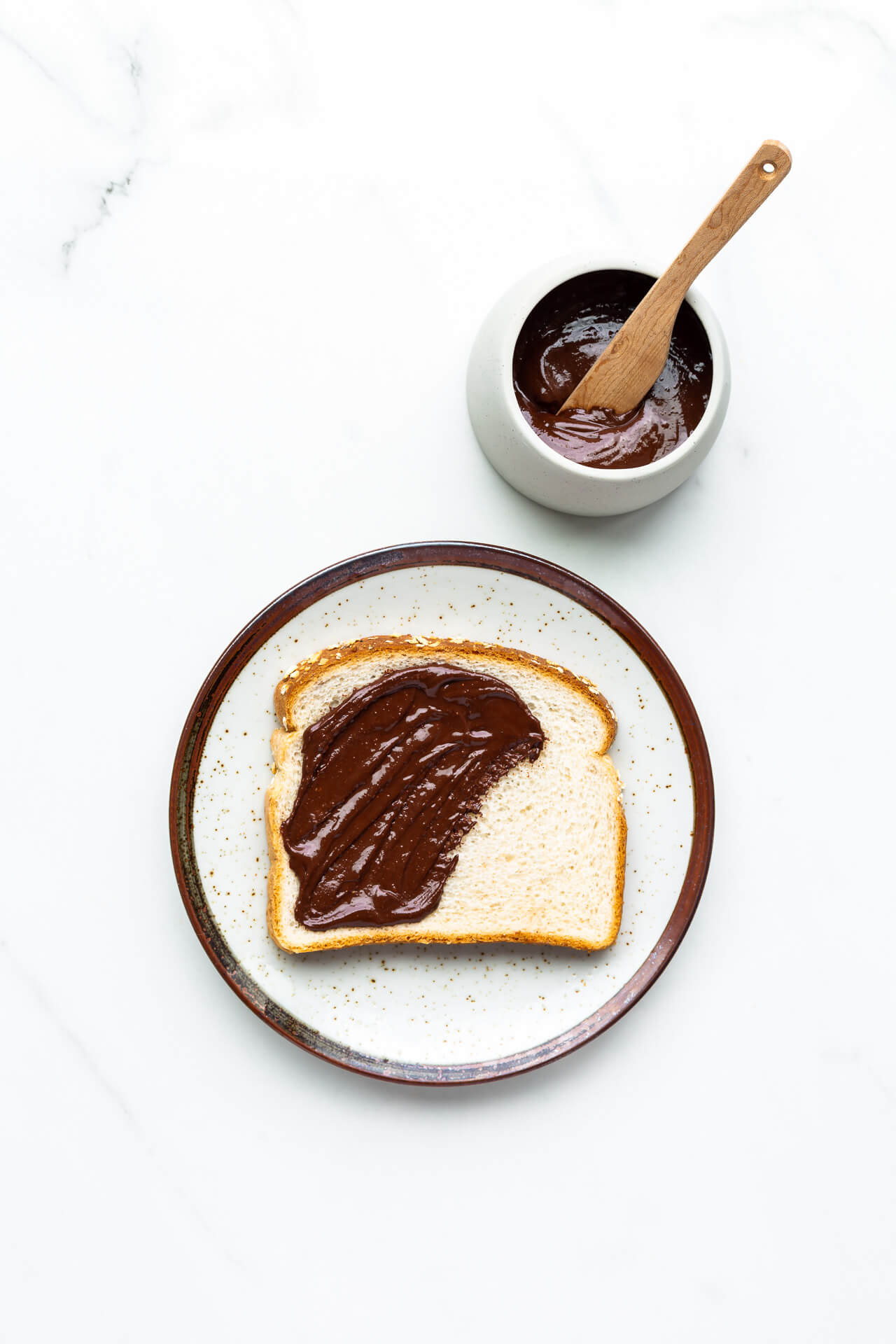 Chocolate peanut butter partly spread on a slice of white sandwich bread set on a ceramic plate with jar of spread and wood knife.