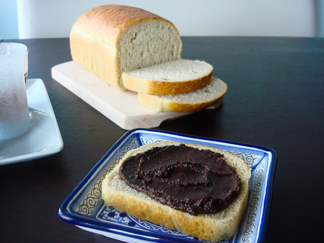 Homemade nutella smeared on a slice of white bread on a blue decorative plate with loaf in background