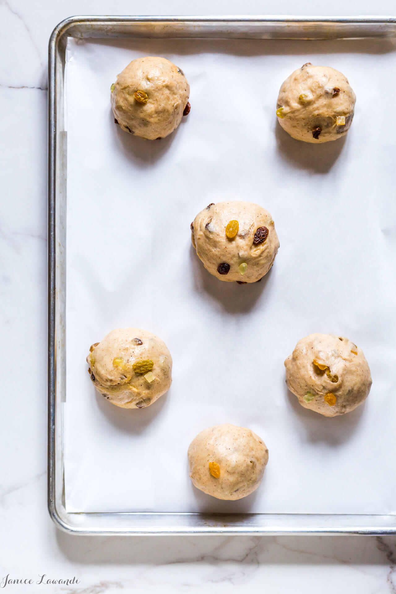 Traditional hot cross buns dough is shaped into buns before rising a second time.