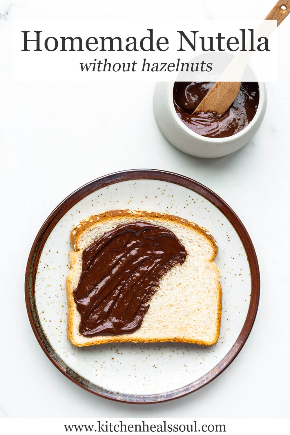Homemade chocolate peanut butter spread on white bread on ceramic speckled plate with brown rim, with bowl of spread and wood knife nearby.