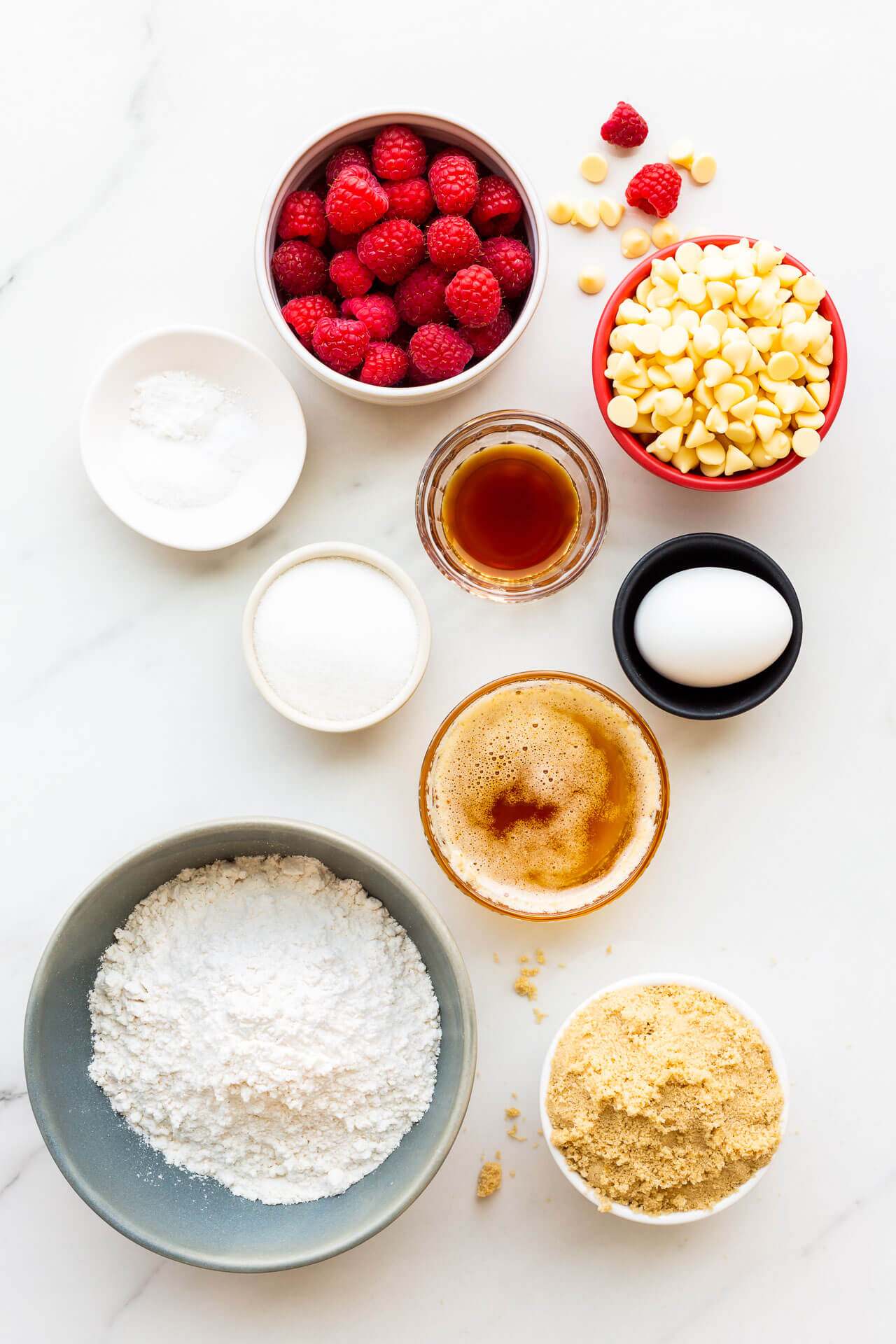 Ingredients measured out to make blondies with fresh raspberries and white chocolate, as well as flour, brown sugar, white sugar, browned butter, salt, baking powder, baking soda,1 egg, vanilla extract.