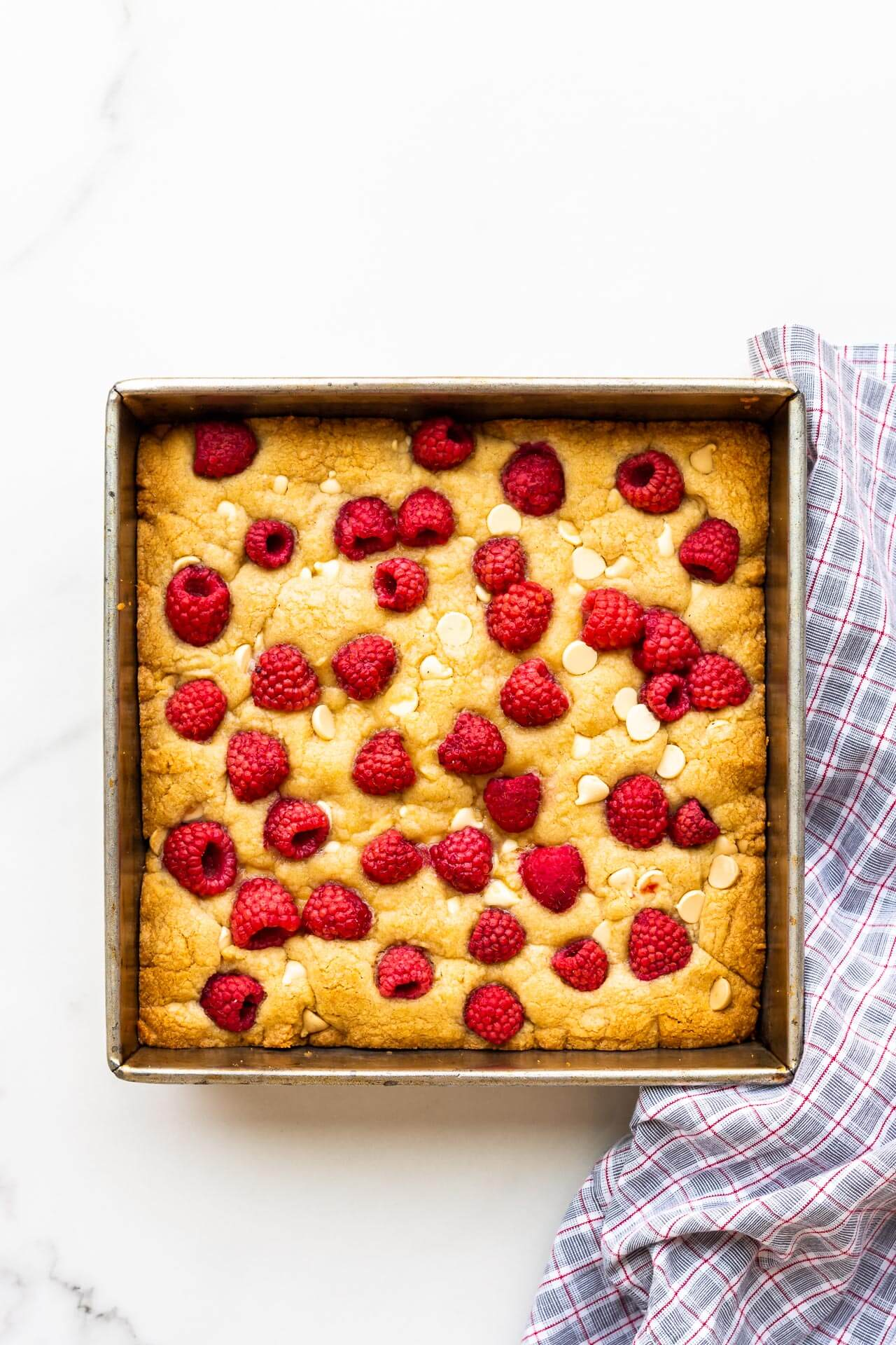 An 8x8 inch pan of baked blondies with raspberries and white chocolate chips on top
