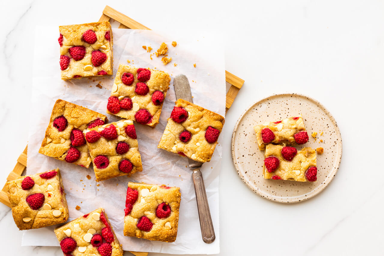 Squares of raspberry white chocolate blondie bars served with a knife on a speckled ceramic plate