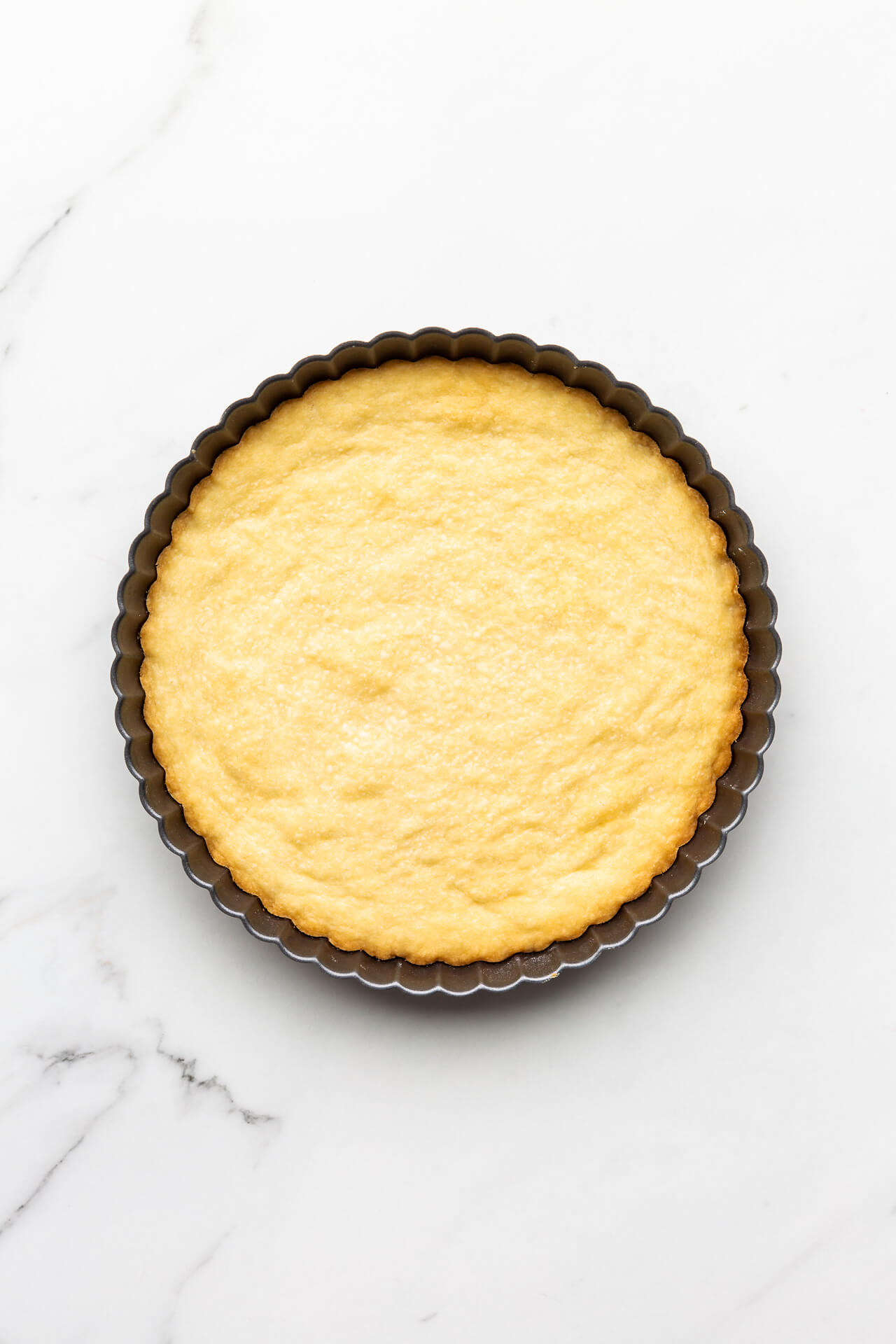 Freshly baked shortbread cookie baked in a fluted tart pan for a crinkly edge
