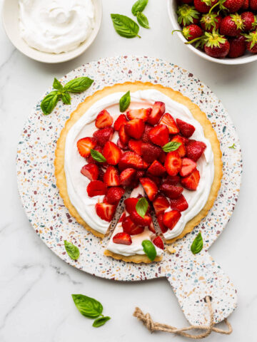 A gorgeous strawberry basil tart served on a terrazzo round board with a bowl of berries and whipped cream on the side