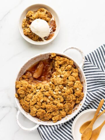 Serving a round white speckled baking dish of apple crisp into white bowls with wooden spoons and blue and white linen