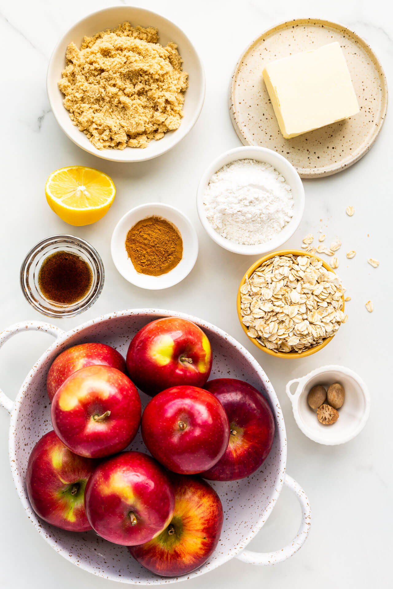 Ingredients to make apple crisp measured out including apples, brown sugar, butter, flour, oats, cinnamon, nutmeg, vanilla bean paste, and a little lemon juice for the apples