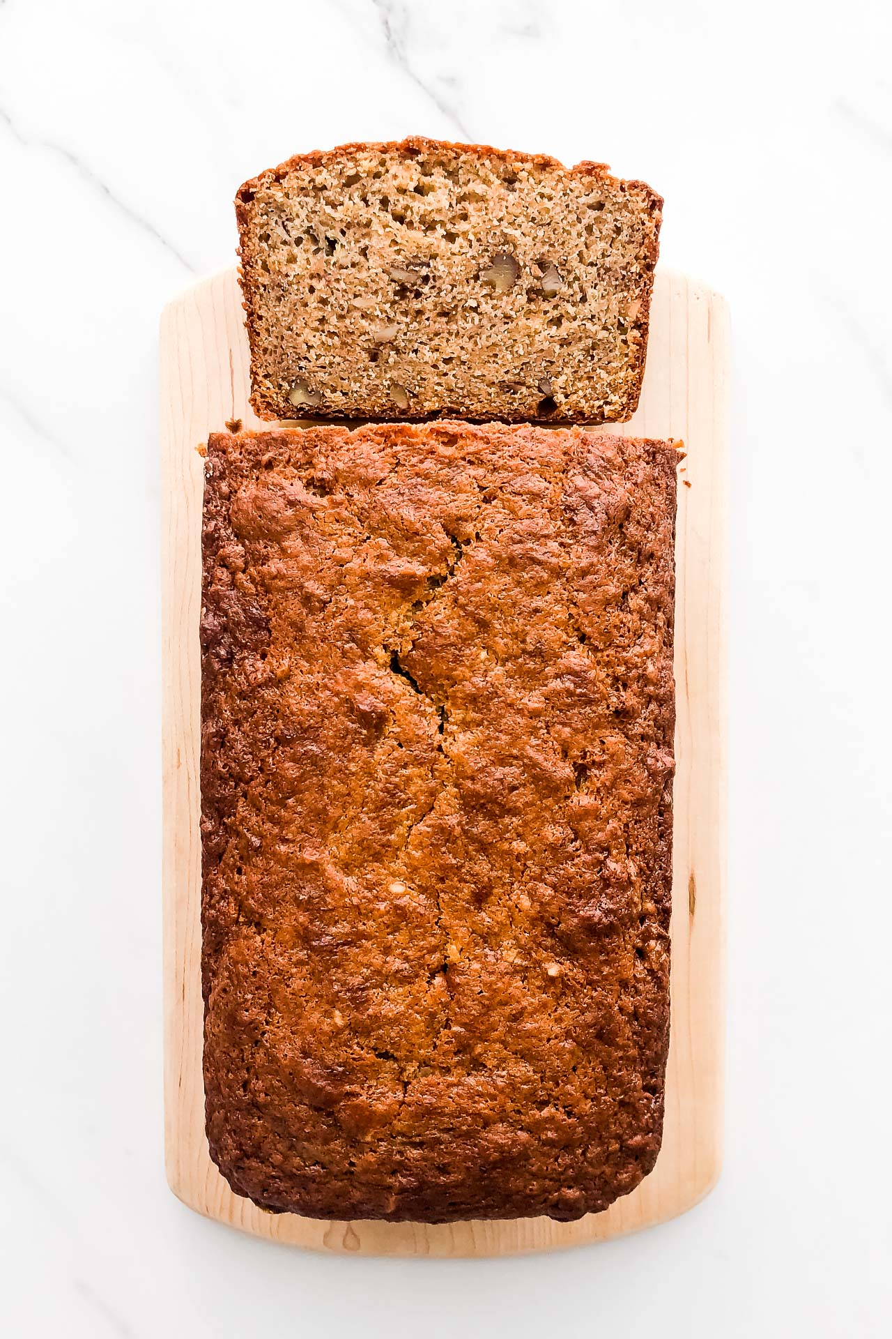 Cardamom banana bread made with sour cream and walnuts, sliced on a wood cutting board