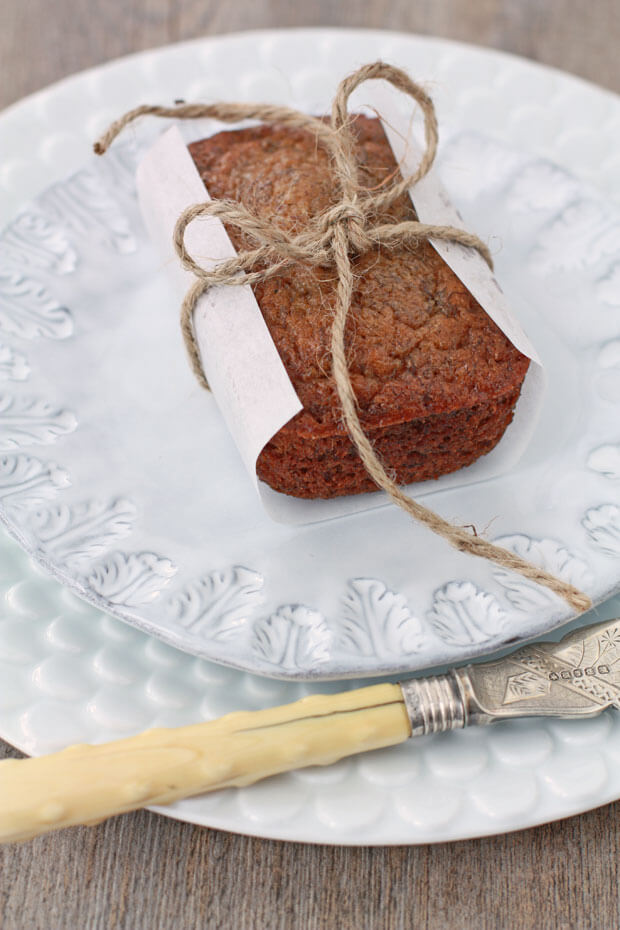 Mini banana bread loaf wrapped in parchment and tied with kitchen twine on a light blue ceramic plate