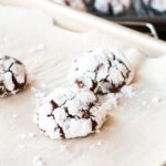 Chocolate crinkle cookies coated in icing sugar on a parchment-lined sheet pan.