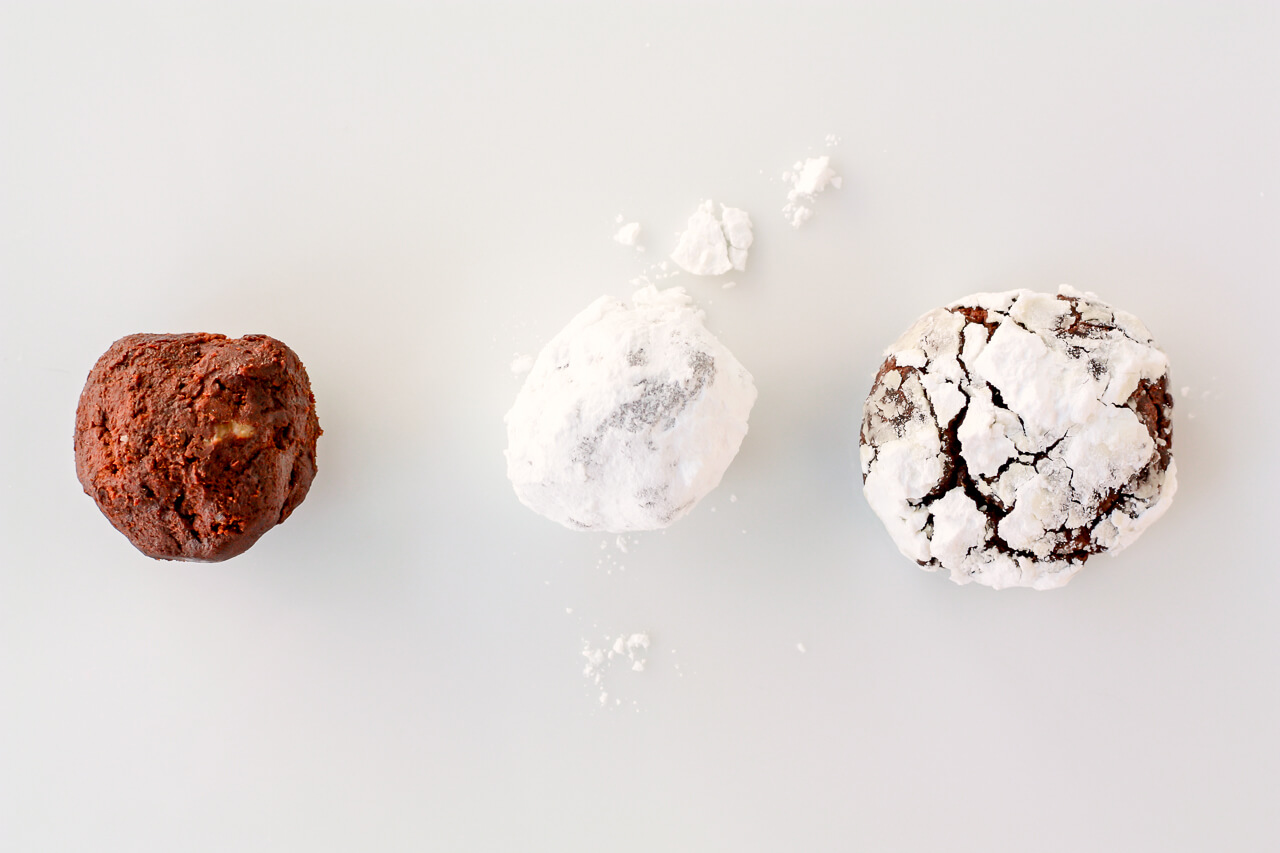 A ball of chocolate cookie dough to show what it looks raw next to a ball coated in powdered sugar before baking next to a baked chocolate crinkle cookie to show the cracked effect on the surface of the cookie.