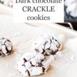 Crackled chocolate crinkle cookies coated in icing sugar on a sheet pan, freshly baked.