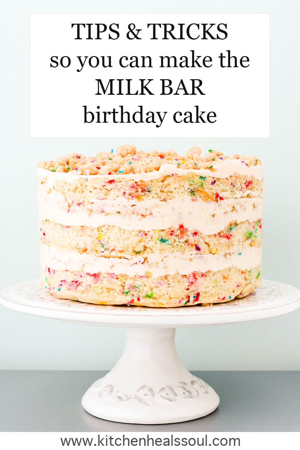 "Milk Bar-style ""naked"" sprinkle birthday cake on a cake stand"