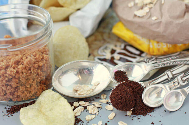 Ingredients for everything cookies or compost cookies include a jar of graham cracker crust, potato chips, oats, chocolate chips, and coffee grinds
