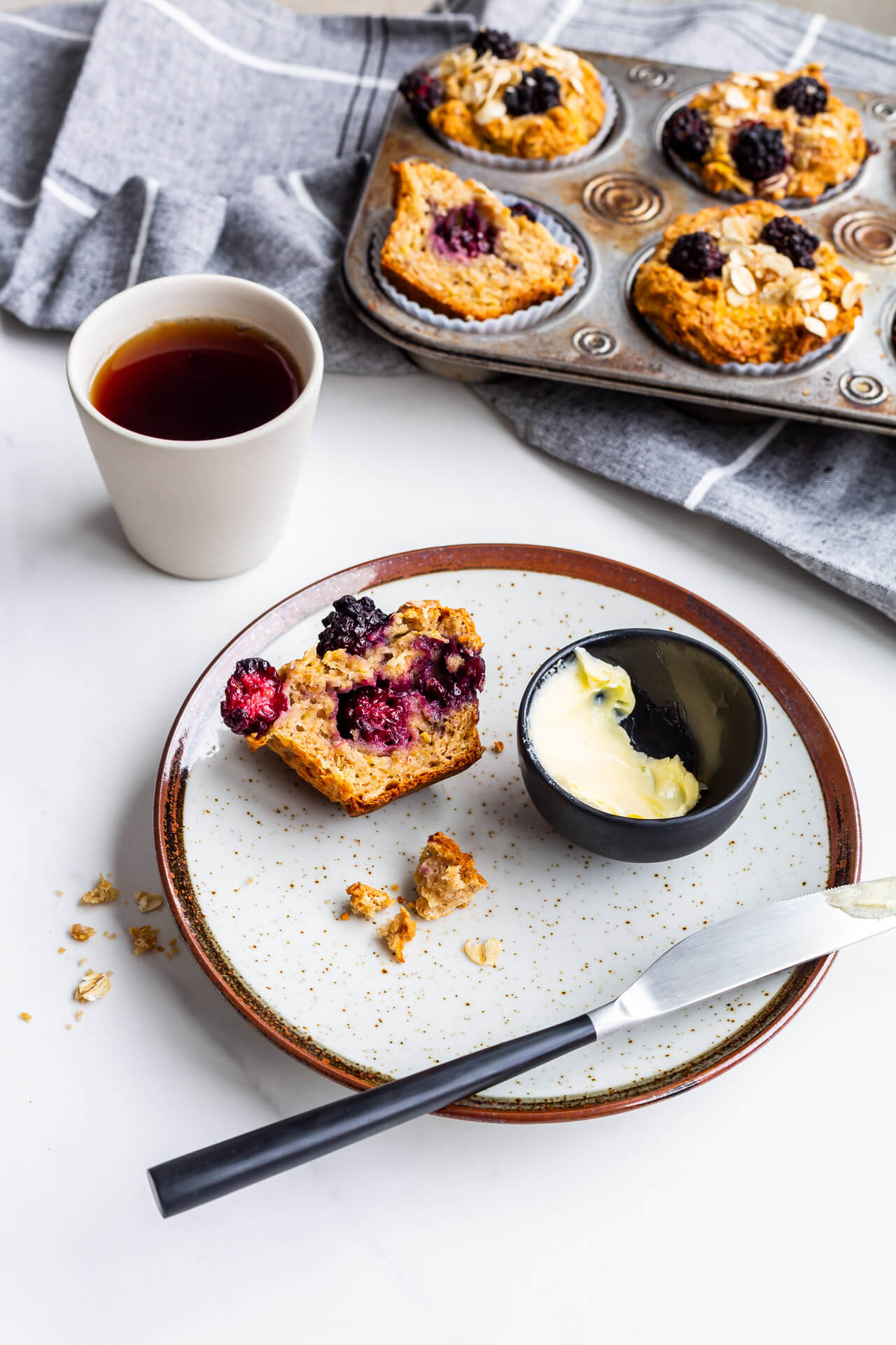 Hearty apple blackberry muffins with oats, one split open on a plate with butter and a knife, served with black tea