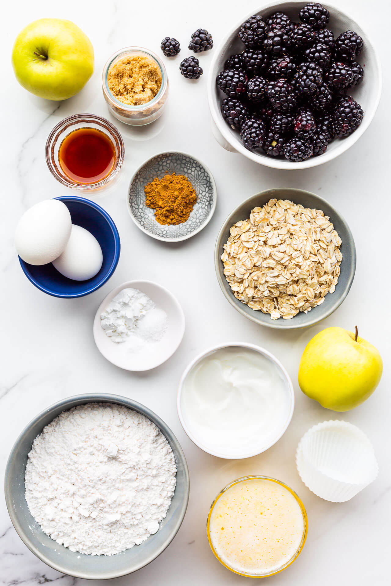Ingredients to make apple blackberry muffins measured out and ready to be mixed, including fresh blackberries, apples, brown sugar, vanilla extract, cinnamon, 2 eggs, baking powder, baking soda, and salt, as well as oats, yogurt, melted butter, flour, and silicone liners for baking