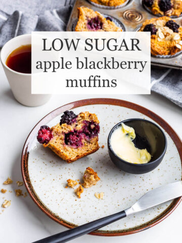 Low sugar apple blackberry muffins with a vintage muffin pan of baked muffins in the background, a cup of black tea, and a speckled ceramic plate with half a muffin and a dish of butter + knife