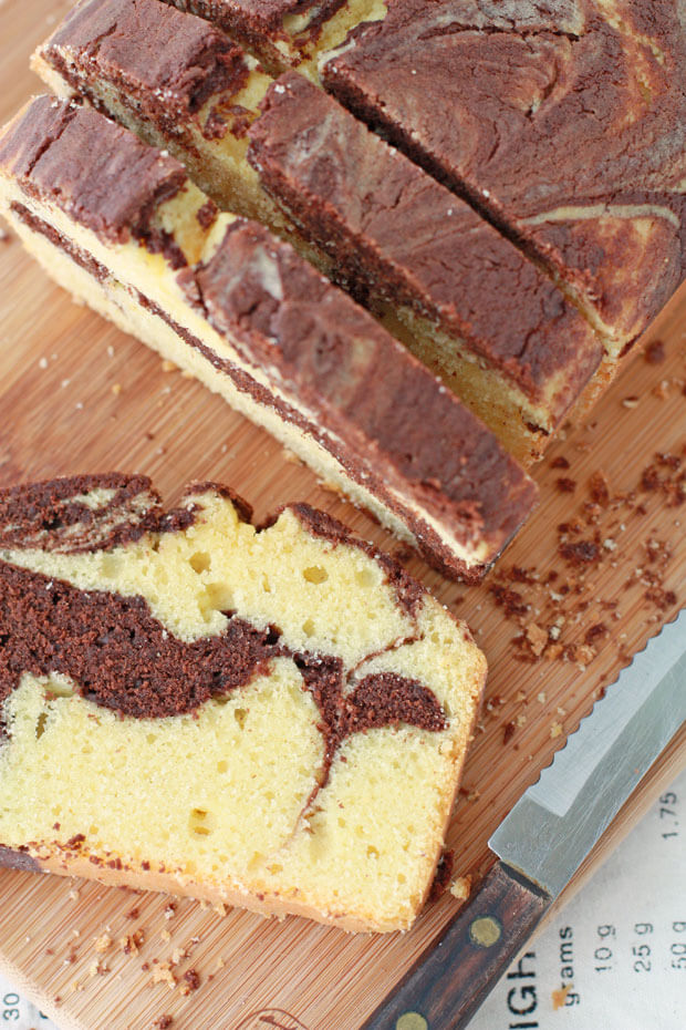 A loaf of chocolate marble cake sliced with a serrated knife