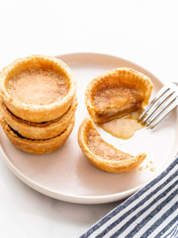 Butter tarts stacked on a beige plate with one cut open with a fork to reveal the gooey filling.