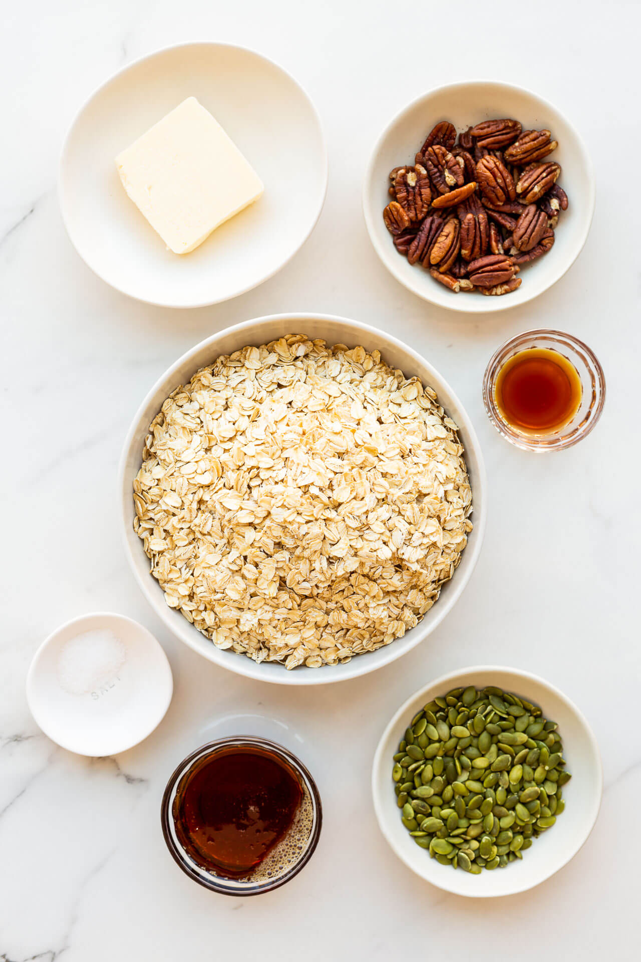 Ingredients to make granola clusters measured out in bowls and ready to be mixed: butter, pecans, vanilla extract, oats, salt, maple syrup, and pumpkin seeds