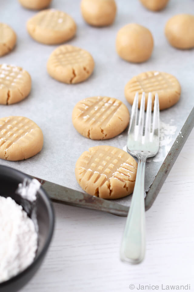 pressing peanut butter cookie dough with a fork for the criss cross pattern