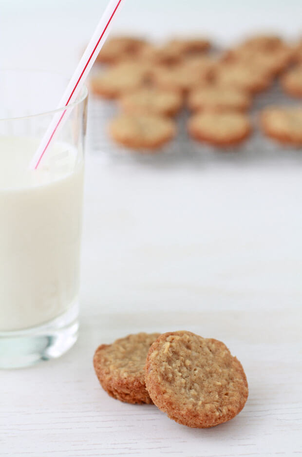 Homemade oatmeal cookies and a glass of milk with more cookies cooling on a rack in the background