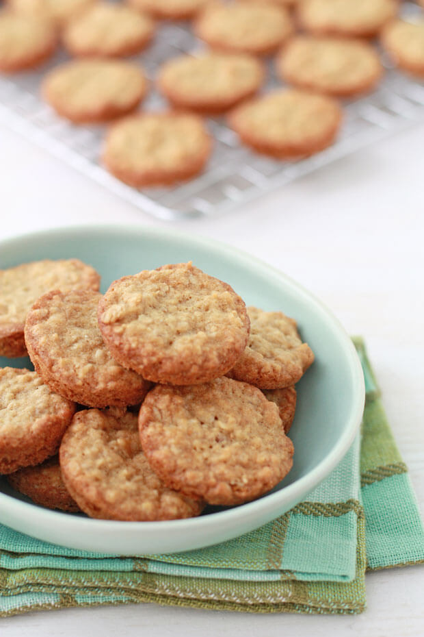 Mini thick oatmeal cookies in a turquoise bowl with more cookies cooling on a wire rack behind