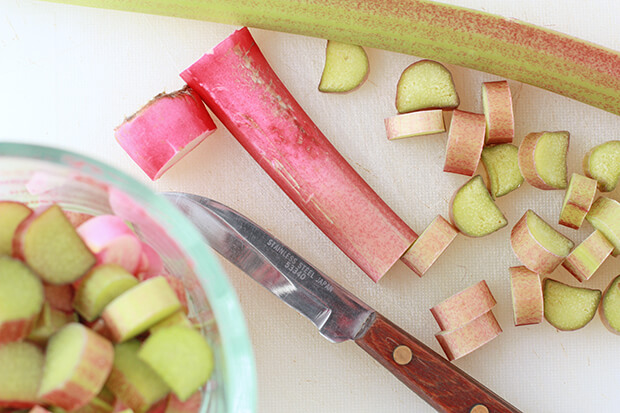 Chopping and slicing fresh rhubarb with a small pairing knife on a white cutting board