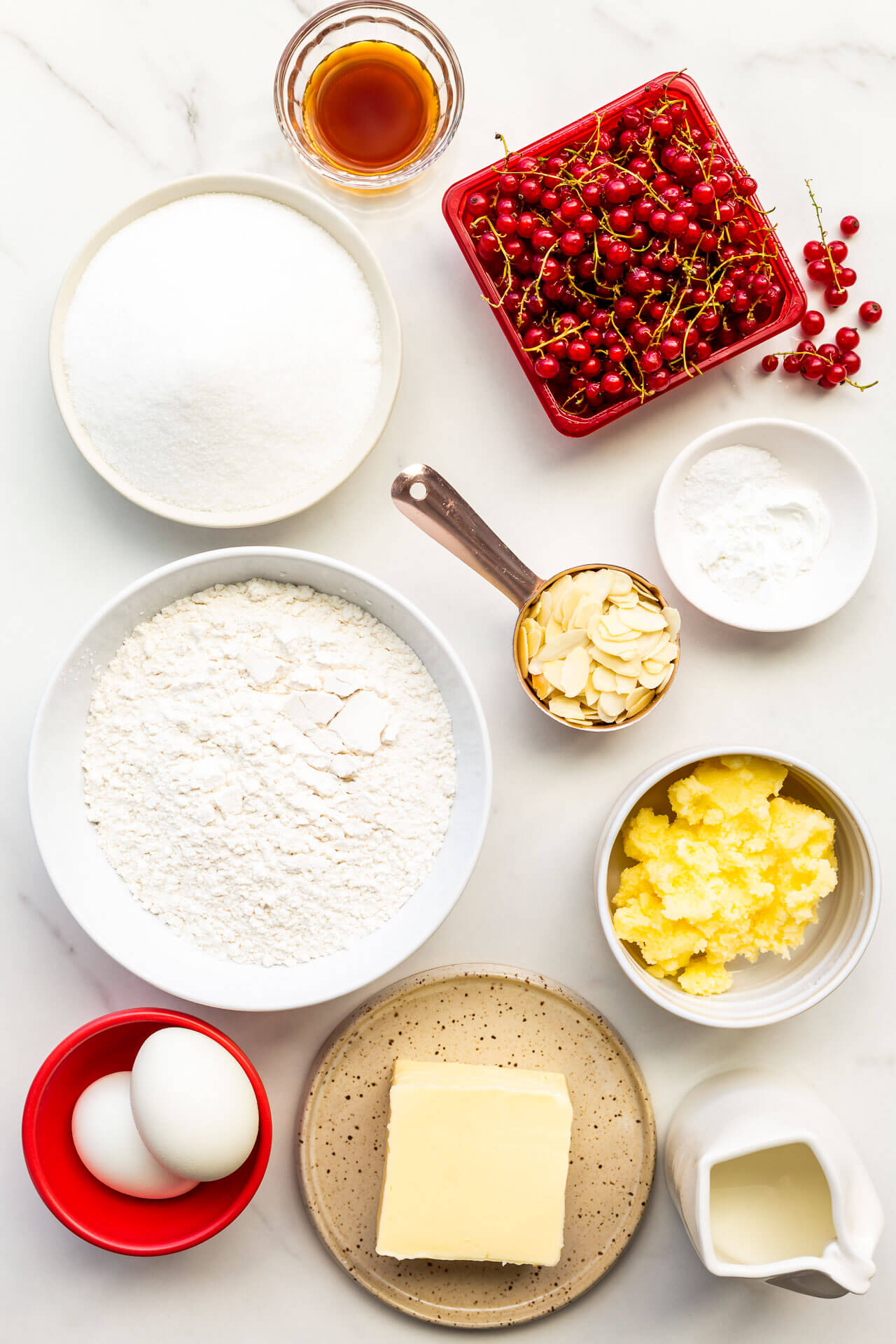 Ingredients measured out in small bowls and plates to make red currant muffins from scratch with a sugary crisp topping and sliced almonds