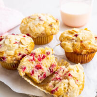 Freshly baked red currant muffins cooling on a parchment-lined wire rack with one open in half and a pink glass of milk in the back