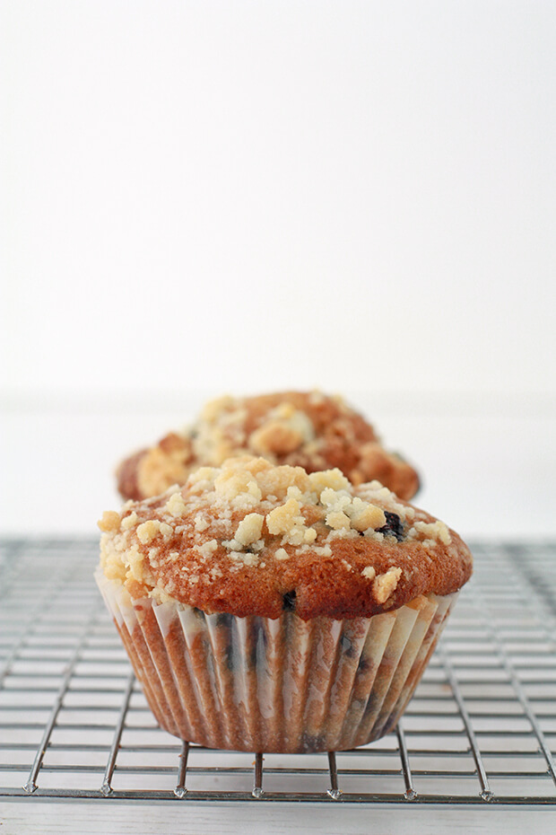 Two blueberry muffins with honey and a crumble topping on a cooling rack. The muffin in the back is taller because it was baked at a higher temperature leading to more of a dome.