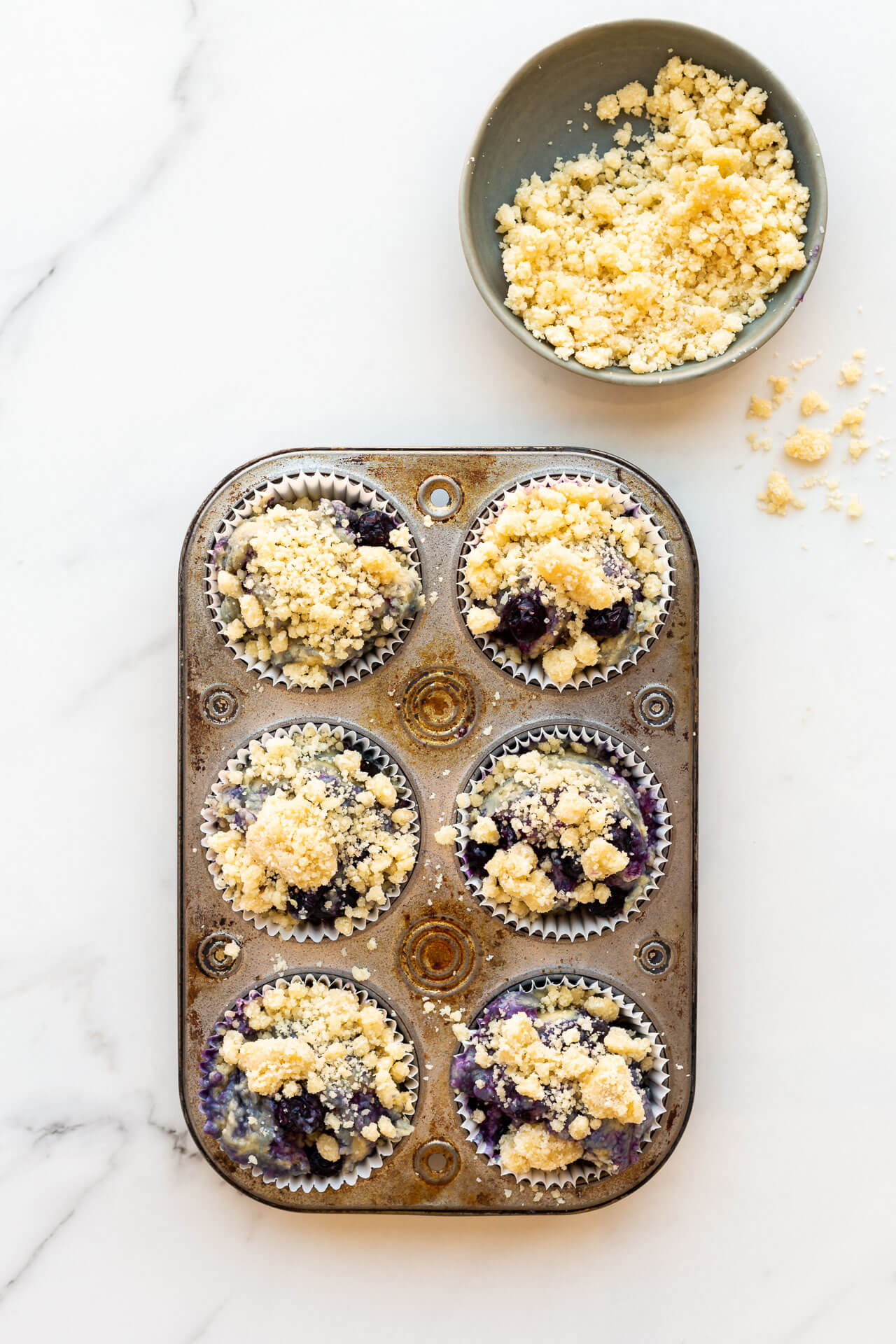 Topping blueberry muffins with streusel topping in a vintage muffin pan before baking