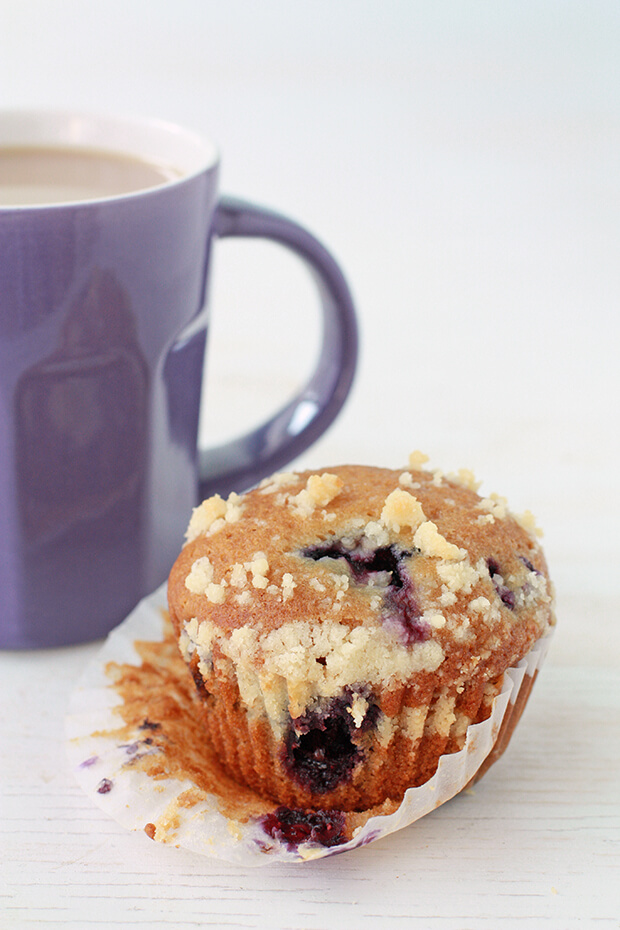Honey blueberry muffins with a crumble topping served with a purple mug of tea