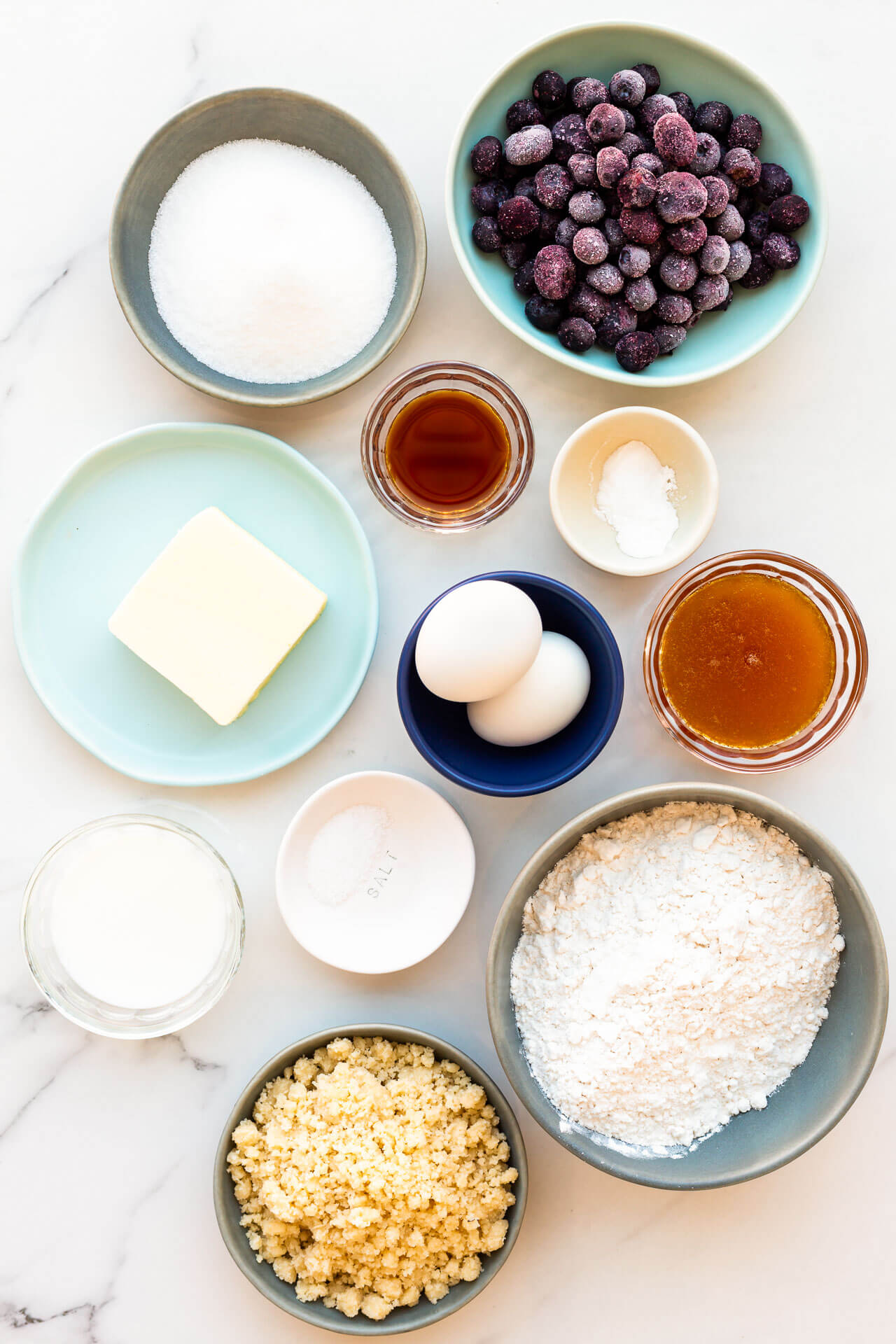 Ingredients laid out for baking blueberry muffins: sugar, frozen blueberries, vanilla, salt, honey eggs, butter, baking powder and soda, flour, and crumble topping