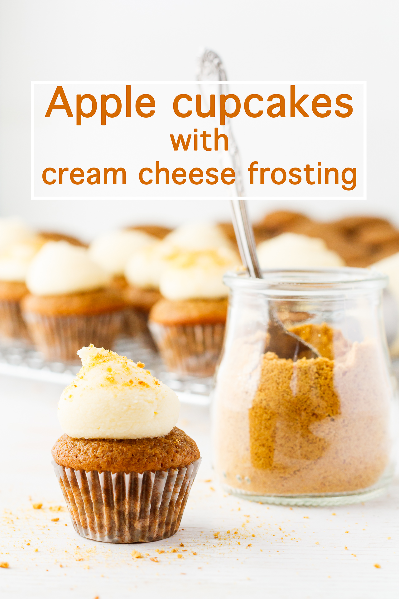 Mini apple cupcakes topped with dollops of cream cheese frosting and sprinkled with spoonfuls of graham cracker crumbs from a jar