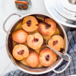 Poached quince cut in half in a sauté pan with simple syrup.