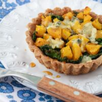 gluten-free tarts filled with kale, squash and topped with cheese