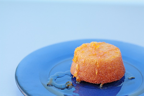 orange almond cake on a blue glass plate served with orange syrup with zest