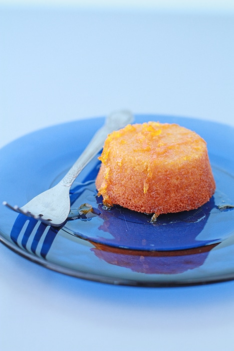 mini orange almond cake with orange syrup served on blue glass plate with fork